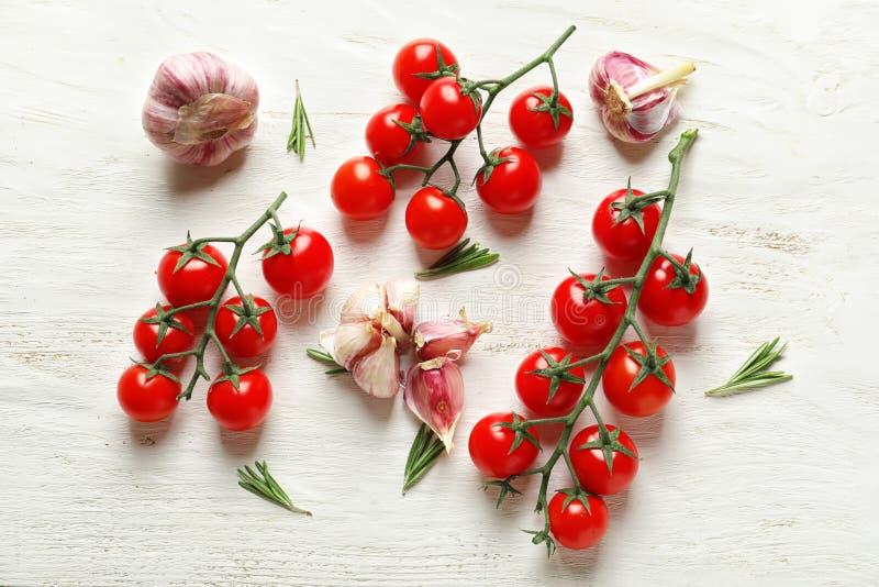 Świezi dojrzali czereśniowi pomidory i czosnek na białym drewnianym tle zdjęcie stock