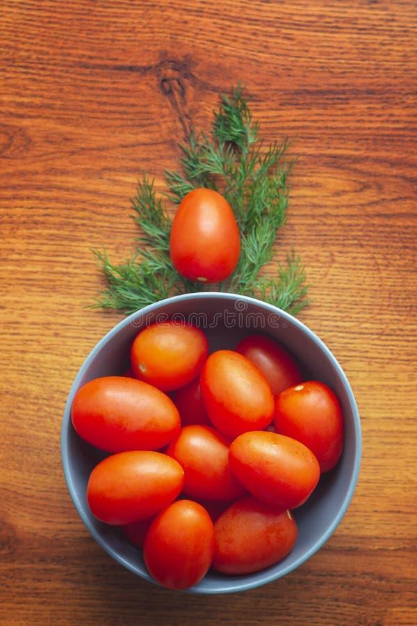 Świezi dojrzali czereśniowi pomidory w błękitnym pucharze z świeżym koperem, koszt stały strzał zdjęcie stock