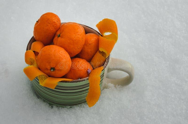 Świezi dojrzali tangerines w wielkim kubku w śniegu Mandaryny w śniegu obrazy royalty free