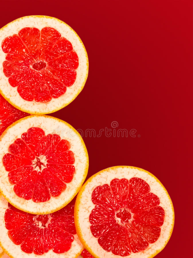 Świezi grapefruitowi plasterki odizolowywający na gradientowej czerwieni zdjęcia stock