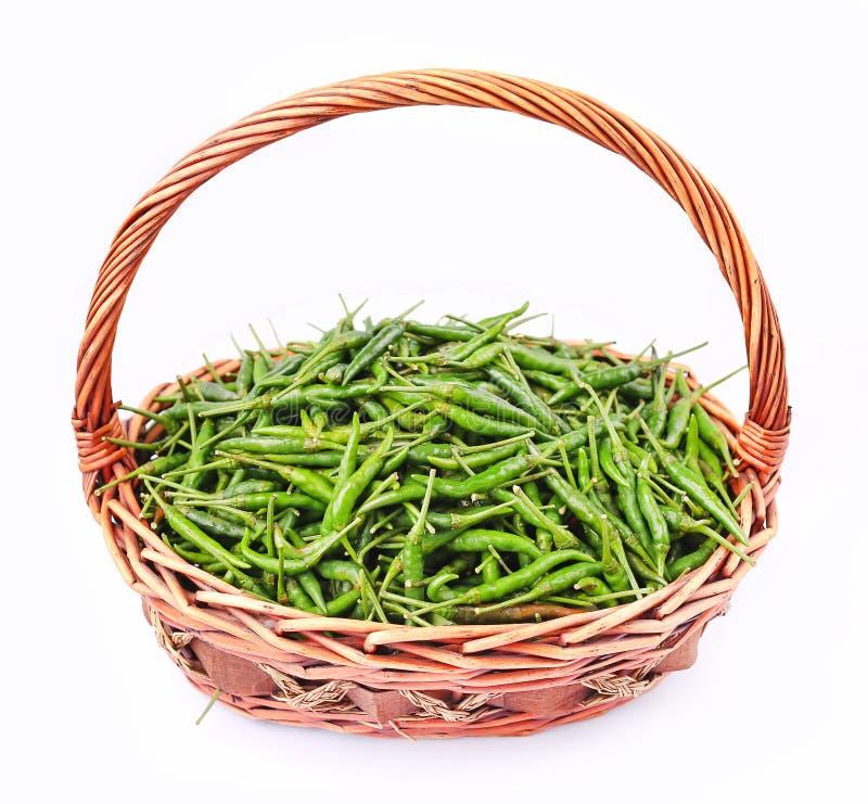 Świezi i korzenni zieleni chili pieprze w rattan koszu obraz stock