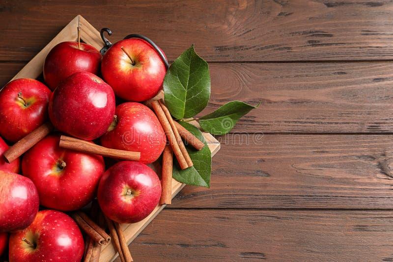 Świezi jabłka i cynamonowi kije na drewnianym stole fotografia stock