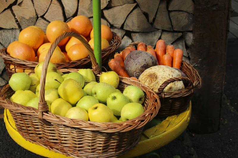 Świezi jabłka, pomarańcze, marchewki i buraki w łozinowych koszach, zbliżają t obrazy royalty free