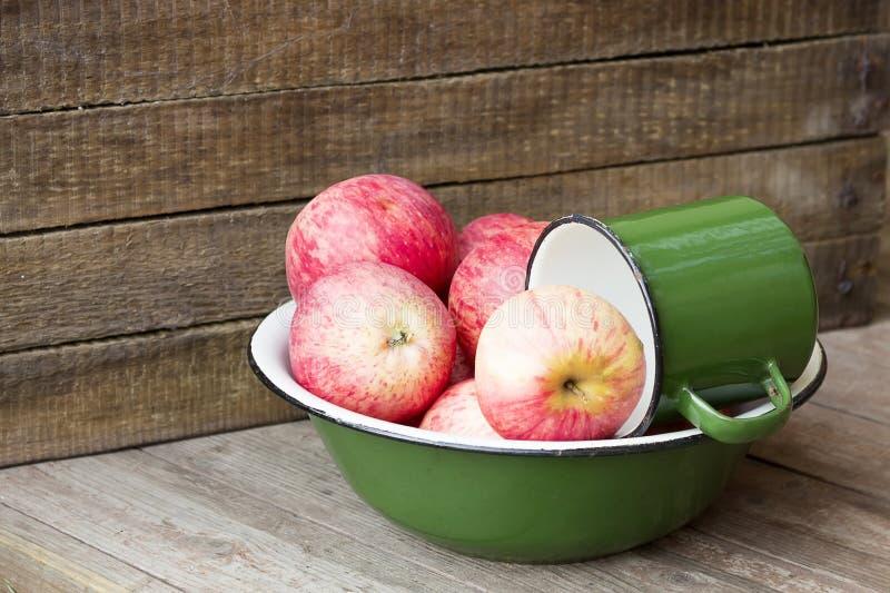 Świezi jabłka w zielenieją blaszanego puchar na drewnianym tle obrazy stock
