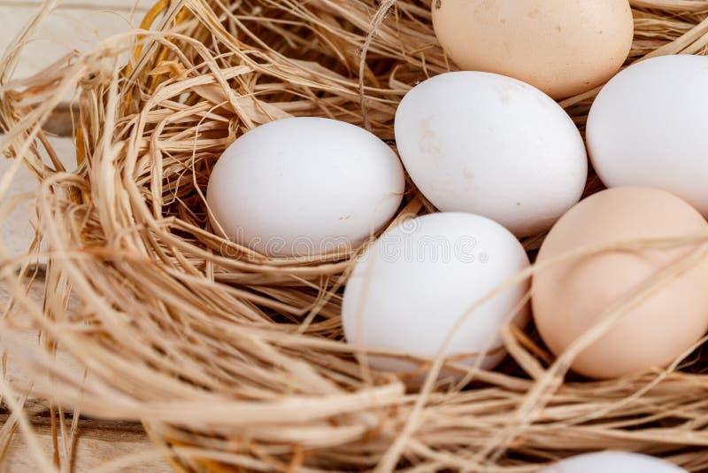 Świezi jajka w koszu z sianem na drewnianym tle zdjęcia stock