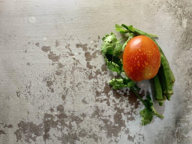 Świezi kolenderów liście, zielony organicznie okra i czerwień pomidor z kroplami woda na starym nieociosanym tle, fotografia royalty free
