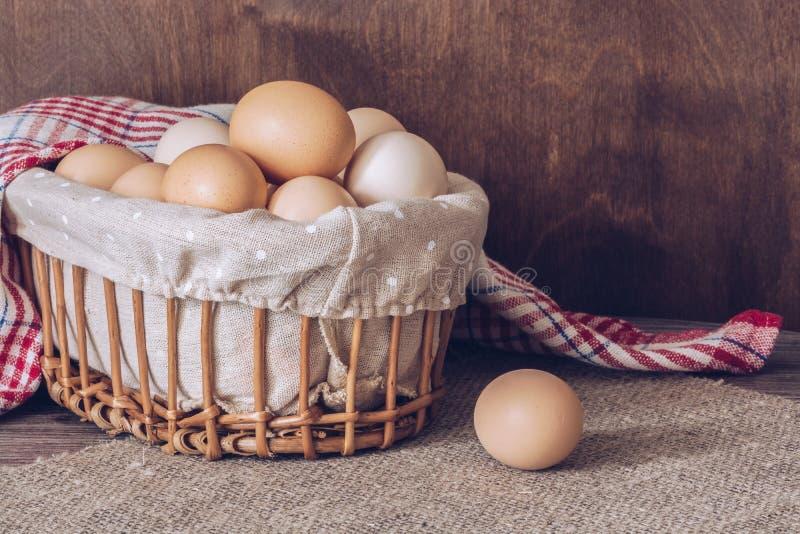 Świezi kurczaków jajka w koszu na drewnianym stole Brezentowa pielucha na stole obrazy stock
