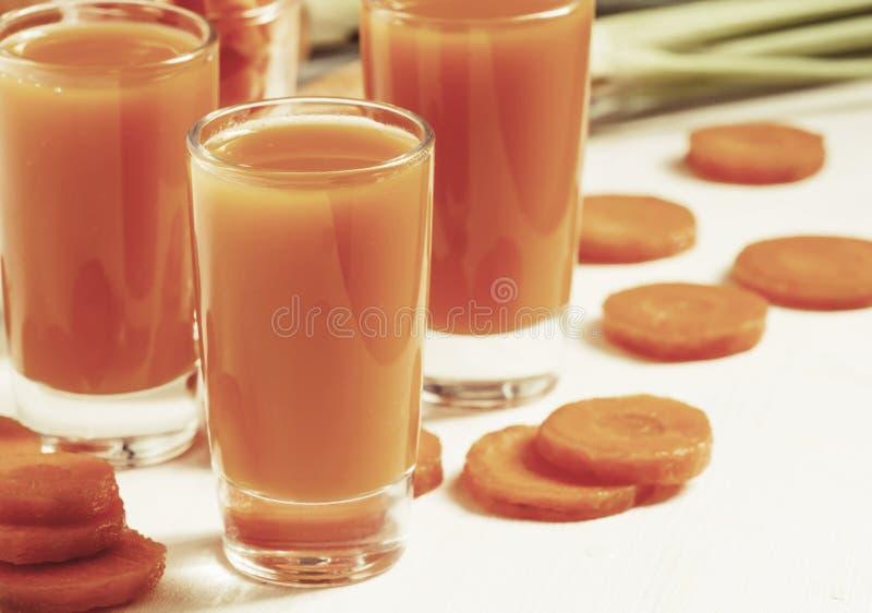 Świezi marchwianego soku szkła na białym drewnianym stole, selekcyjna ostrość zdjęcie royalty free