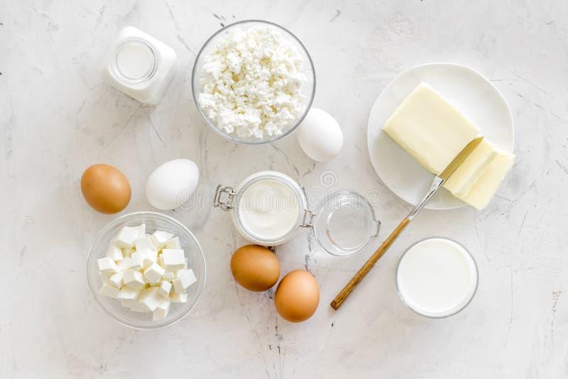 Świezi nabiały dla śniadania z mlekiem, chałupa, jajka, masło, yougurt na bielu marmuru tła odgórnego widoku egzaminie próbnym w  fotografia stock