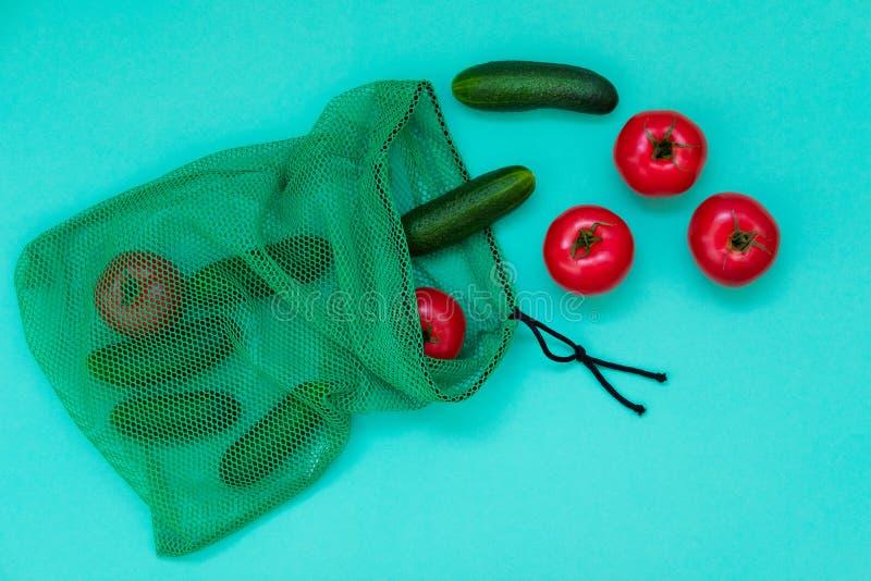 Świezi ogórki i pomidory spada z zakupy zarabiają netto obrazy stock