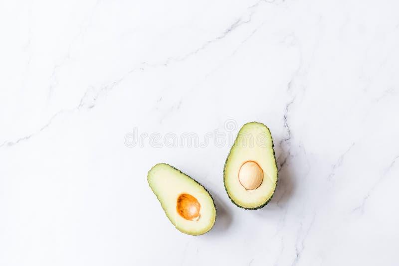 Świezi organicznie hass avocados kłama na białym marmurowym tle, kreatywnie mieszkania nieatutowy zdrowy karmowy pojęcie, kopii p obraz royalty free