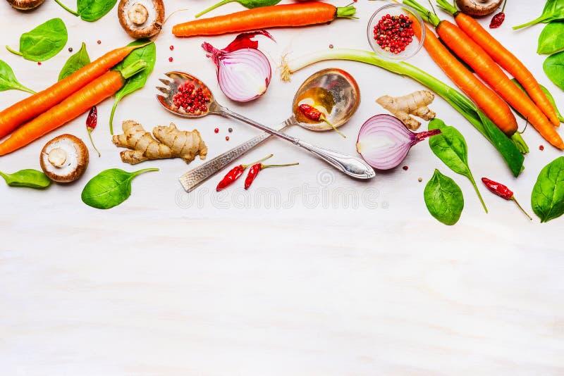 Świezi organicznie warzywa i łyżki na białym drewnianym tle, odgórny widok, granica fotografia stock