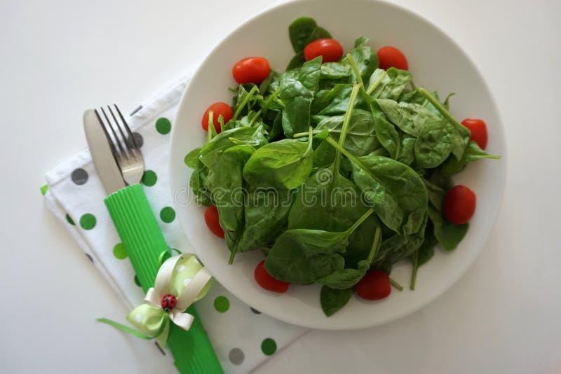 Świezi organicznie zieleni szpinaków liście słuzyć na talerzu Zdrowy jedzenie i ?asowania poj?cie fotografia royalty free