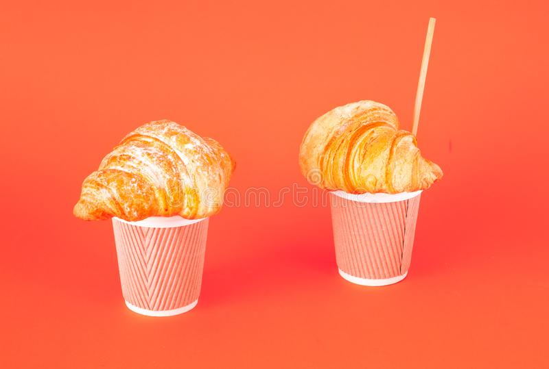 Świezi piec croissants i kawa w papierowych filiżankach z drewnianą tubką na koralowym tle Kolor 2019 fotografia stock