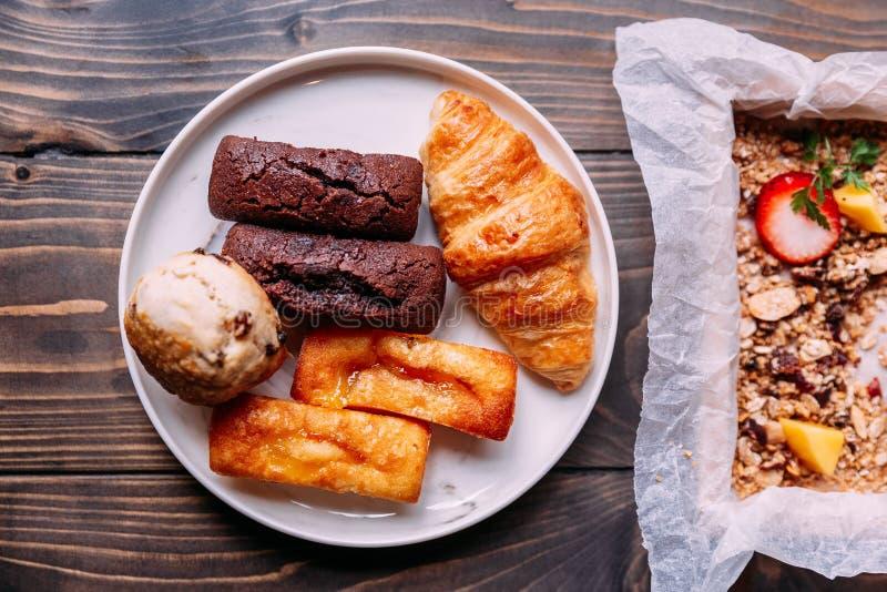 Świezi piec towary na białym naczyniu wliczając scone, croissant, finansisty i czekolada finansisty, obrazy stock