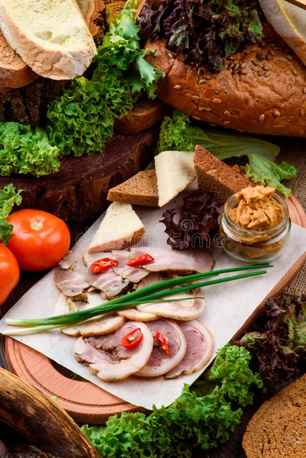 Świezi plasterki wyśmienicie bekon, horseradish, croutons zmrok i lekki chleb na lekkiej drewnianej desce, obraz royalty free