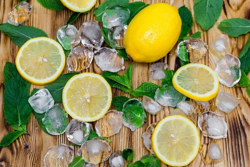 Świezi pokrojona cytryna, jaskrawa - zielona mennica i lód na drewnianym stole Mojito koktajlu bezalkoholowi ingridients Orzeźwie obraz stock
