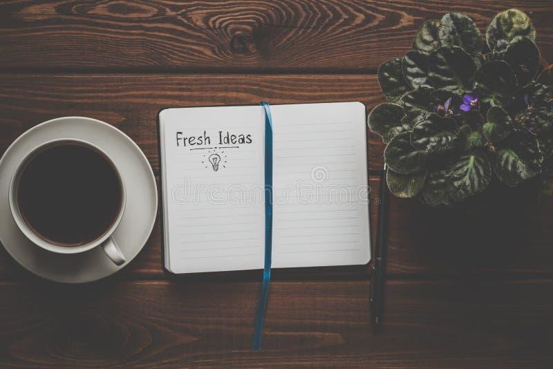 Świezi pomysły - słowa na otwartym notatniku na drewnianym stole z filiżanką kawy, odgórny widok Inspiruje i twórczości pojęcie fotografia stock