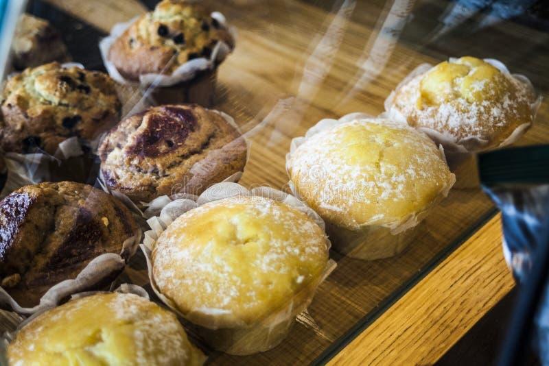 Świezi różnorodni muffins na drewnianym tle Odgórny widok zdjęcia stock