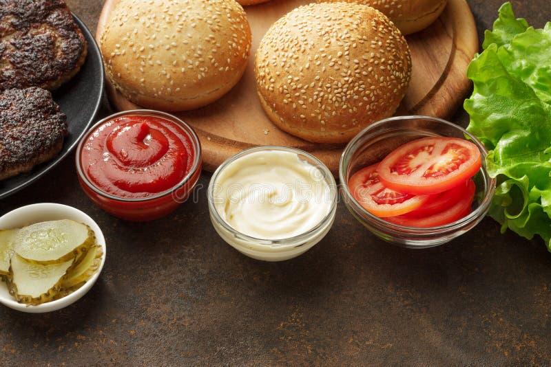 Świezi składniki dla hamburgerów: babeczki, cutlet, kumberlandy, warzywa i sałatka, zdjęcia stock