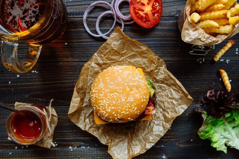 Świezi smakowici hamburgery z francuskimi dłoniakami, kumberlandem i piwem na drewnianym stołowym odgórnym widoku, obrazy royalty free