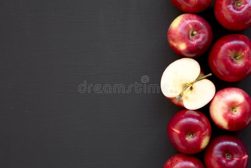 Świezi surowi czerwoni jabłka na czarnym tle, odgórny widok Mieszkanie nieatutowy, zasięrzutny, od above kosmos kopii obraz royalty free
