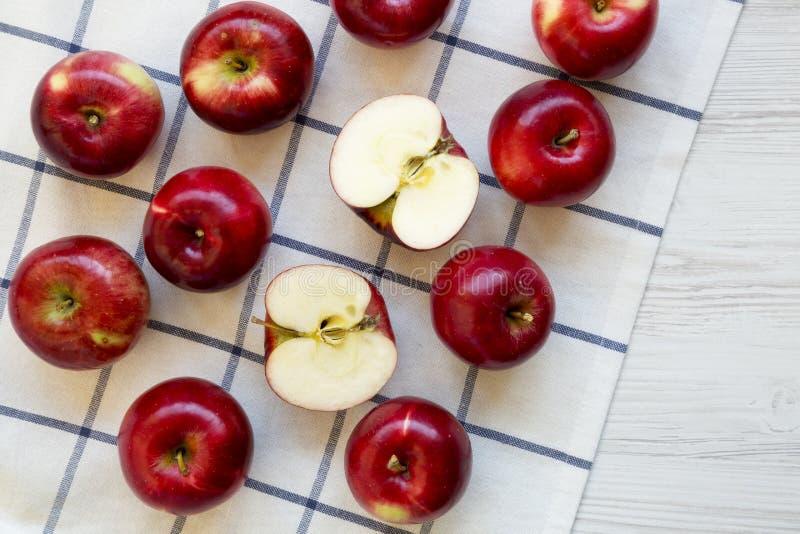 Świezi surowi organicznie czerwoni jabłka na płótnie nad białym drewnianym tłem, odgórny widok Mieszkanie nieatutowy, od above, k zdjęcie stock