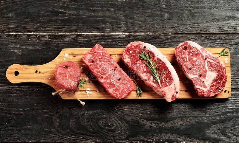 Świezi surowi Pierwszorzędni Czarni Angus wołowiny stki na drewnianej desce zdjęcie royalty free