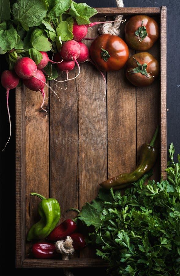Świezi surowi składniki dla zdrowy kulinarnego lub sałatka robi w nieociosanej drewnianej tacy nad czarnym tłem, odgórny widok, k obraz stock