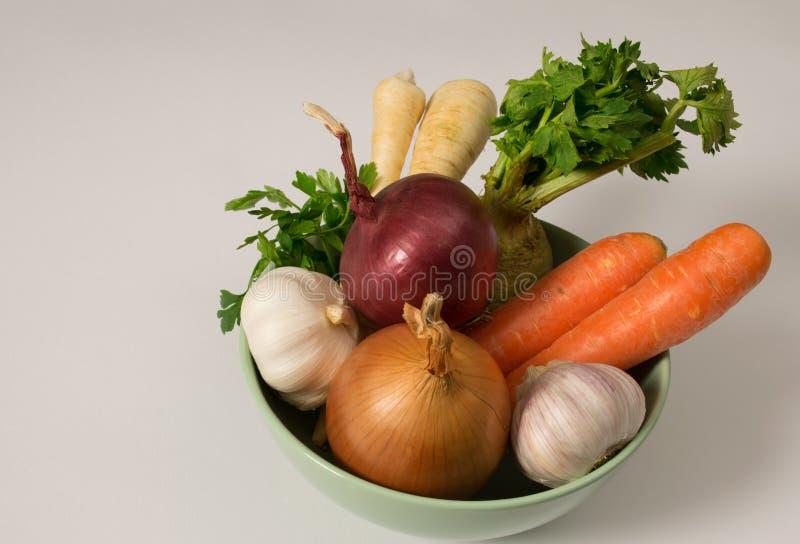 Świezi surowi warzywa, marchewka, cebula, czosnek, seler i pietruszka w naczyniu na białym tle, zdjęcia royalty free