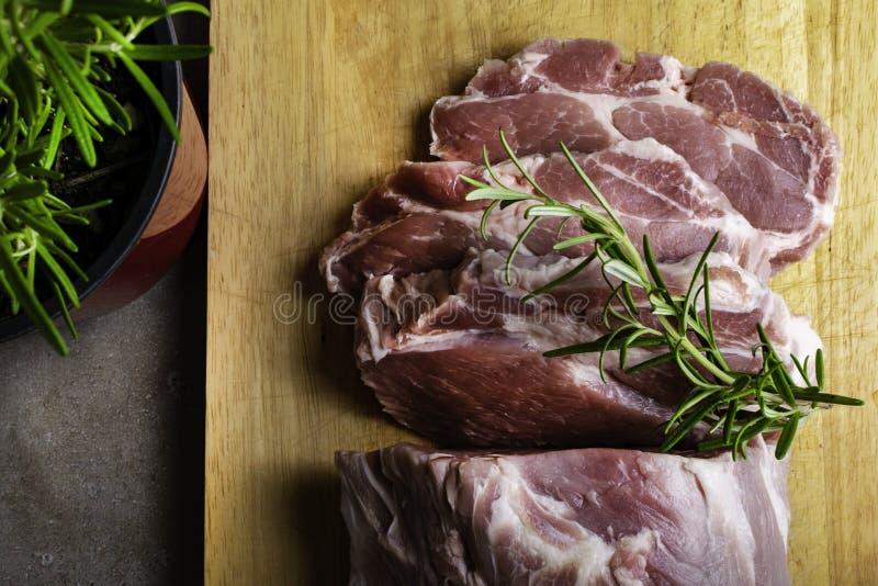 Świezi surowi wieprzowina kotleciki na ciąć drewnianą deskę z rozmarynami obraz stock