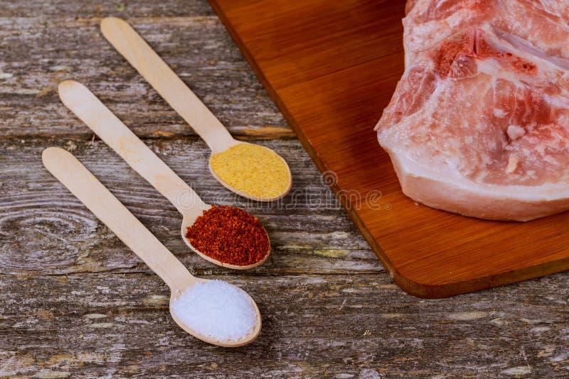Świezi uncooked wieprzowina kotleciki na krytykują talerza, ziele i pikantność, zdjęcia stock