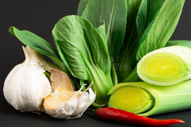 Świezi warzywa: bok choy chińska kapusta, leek, chili pieprz i czosnek na czarnym tle, zdrowa żywność zdjęcie royalty free