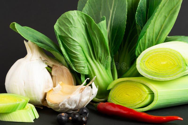Świezi warzywa: bok choy chińska kapusta, leek, chili pieprz i czosnek na czarnym tle, zdrowa żywność obrazy stock