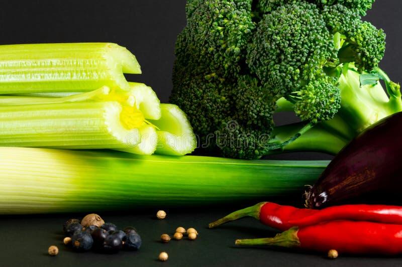 Świezi warzywa na czarnym tle: brokuły, seler, leek, czerwona cebula, chili pieprz inne przyprawy zdrowa żywność obrazy royalty free