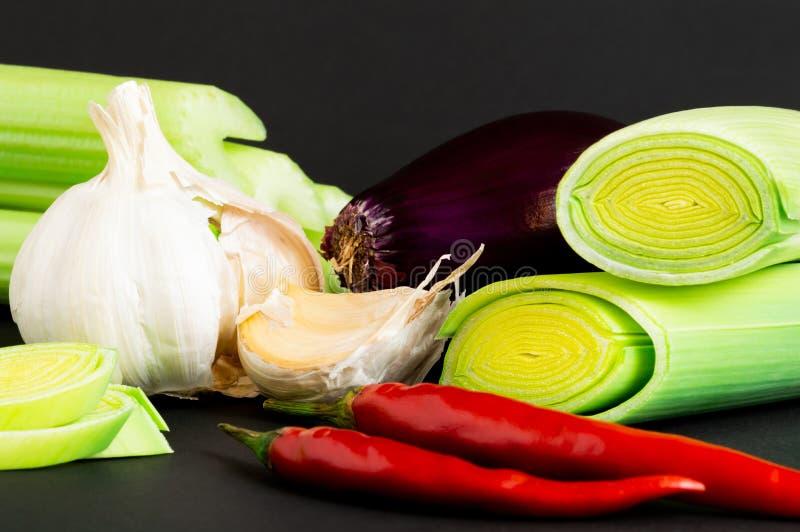 Świezi warzywa na czarnym tle: seler, leek, czerwona cebula, chili pieprz i czosnek, zdrowa żywność obrazy royalty free