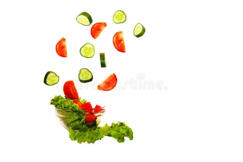 Świezi warzywa spada w talerz na białym tle w zwolnionym tempie fotografia stock