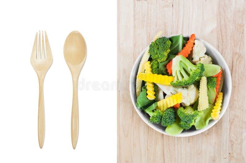Świezi warzywa w białym pucharze z drewnianą łyżką i rozwidleniu odizolowywającym na bielu obrazy royalty free