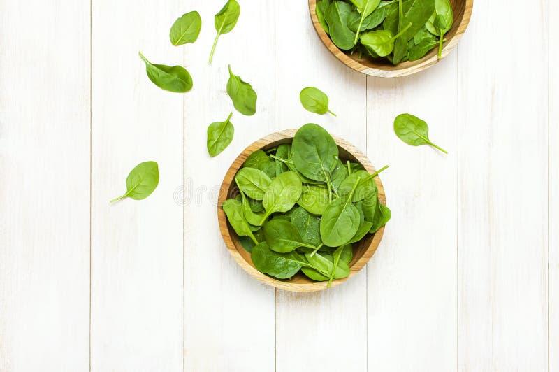 Świezi zieleni szpinaków liście na drewnianym pucharze na białej drewnianej nieociosanej tło odgórnego widoku kopii przestrzeni D fotografia royalty free