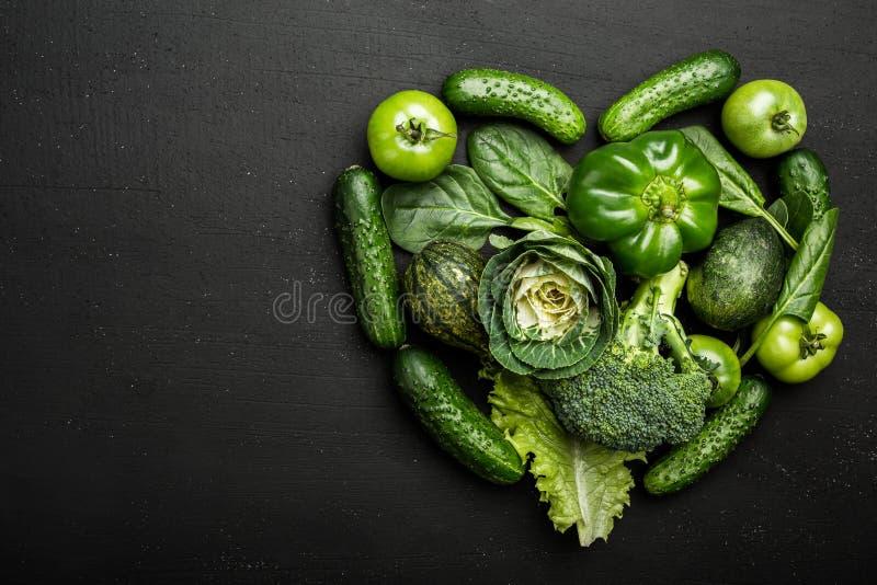 Świezi zieleni warzywa na czarnym stole fotografia royalty free