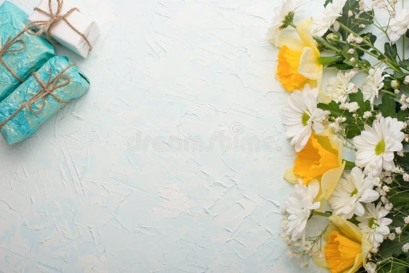 Żółci daffodils z prezentami na drewnianym tle, odgórnym widoku z pustą przestrzenią dla pisać lub reklamować, zdjęcie stock