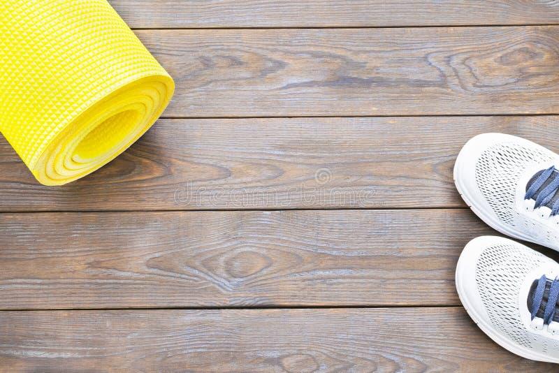 Żółci joga sporta i maty buty na ciemnego brązu drewnianym tle zdjęcie stock
