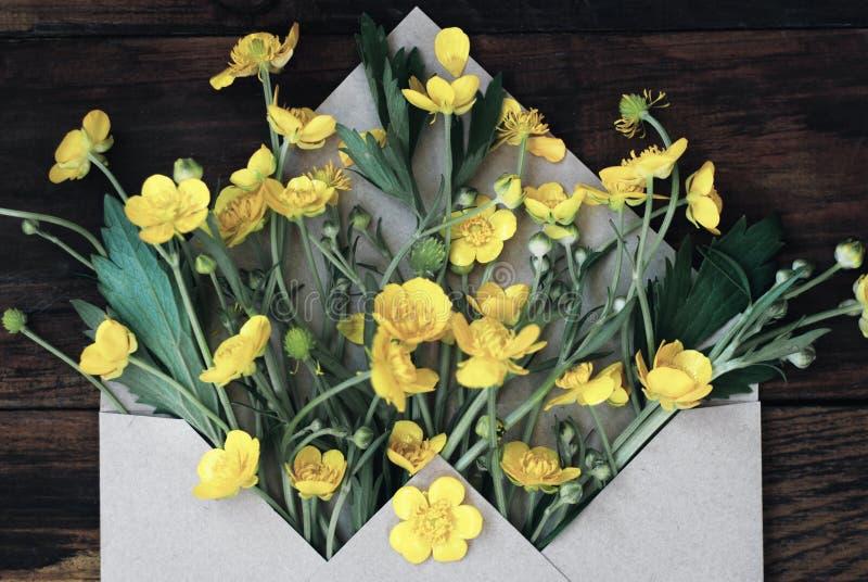 Żółci Mali kwiaty w Kopertowym Nieociosanym Drewnianym tło sztandaru mieszkaniu Lay fotografia royalty free