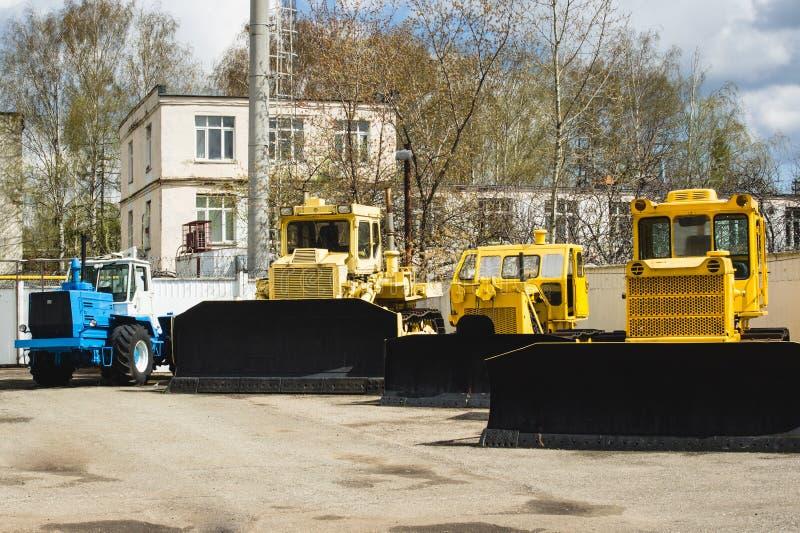 Żółci przemysłowi ciągniki w jardów Rosyjskich przemysłowych ciągnikach z buldożerami obraz royalty free