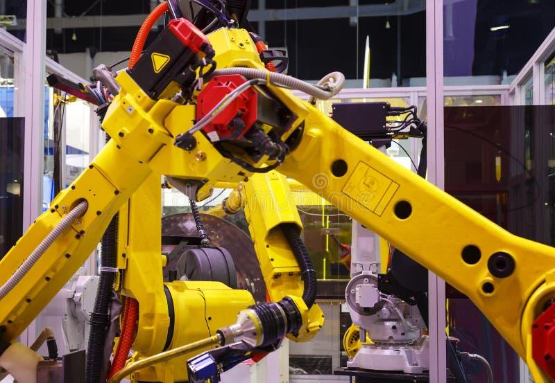 Żółci roboty przetwarzają metal części w linii produkcyjnej obraz stock