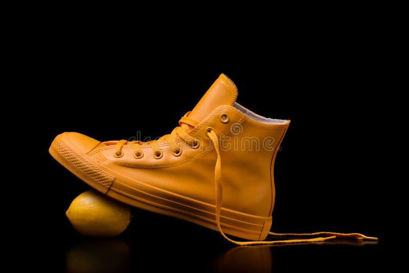 Żółci sneakers z soczystą cytryną na czarnym tle zdjęcia royalty free
