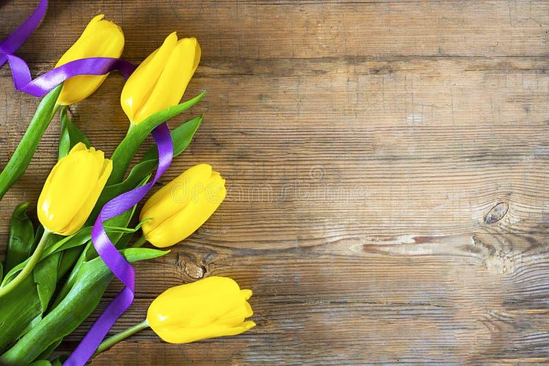 Żółci tulipany z fiołkowym faborkiem na lewej części stary drewniany textured tło z kopii przestrzenią dla teksta lub projekta ró zdjęcia royalty free