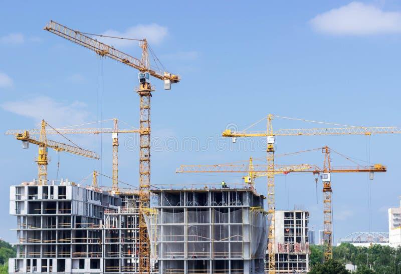 Żółci wysocy żurawie, budowa wieżowowie zdjęcie royalty free