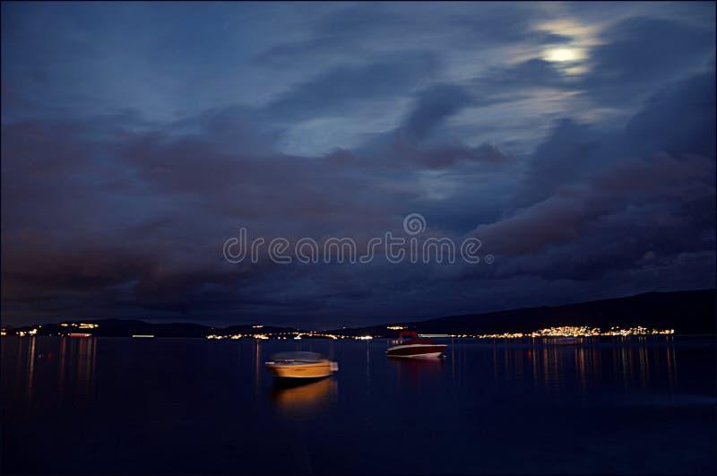 Żółta łódź na wodzie Kotor zatoka przy nocą z odbiciem brzeg lampiony i księżyc w chmurach obrazy stock