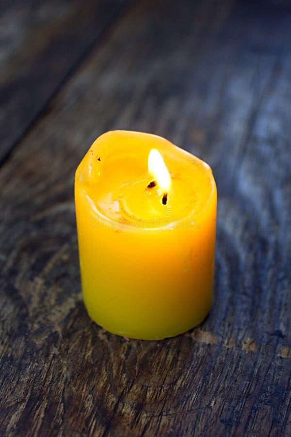 Żółta świeczka na drewnianej desce obraz royalty free